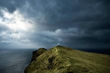 Lighthouse Under Dramatic Sky On Sea Cliff, Faroe Islands