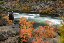 Man With Backpack Along Deschutes River At Dillon Falls In Fall