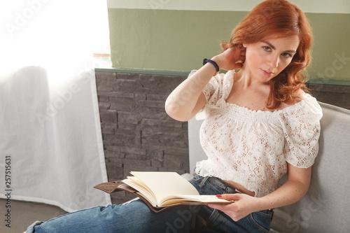 Photo bella ragazza rossa sfoglia un libro seduta sul divano
