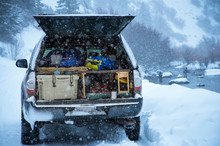 Various Gear Lying Inside Open Trunk Of Truck Parked Beside River During Snowstorm, Basalt, Colorado, USA