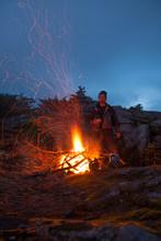 Portrait Of A Climber Keeping Warm Beside An Alpine Bonfire