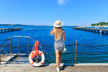 Young Girl Standing On The Pier Near The Lifebuoy And Looking At