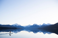 Man Paddleboarding On Lake McDonald, Montana, USA