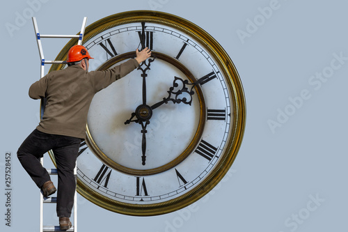 Man is standing on a ladder and adjusting the clock #257528452