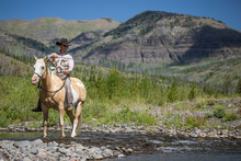 A Man Fishes From The Back Of A Pinto Horse In Cowboy Hat In Montana Backcountry Near Yellowstone.