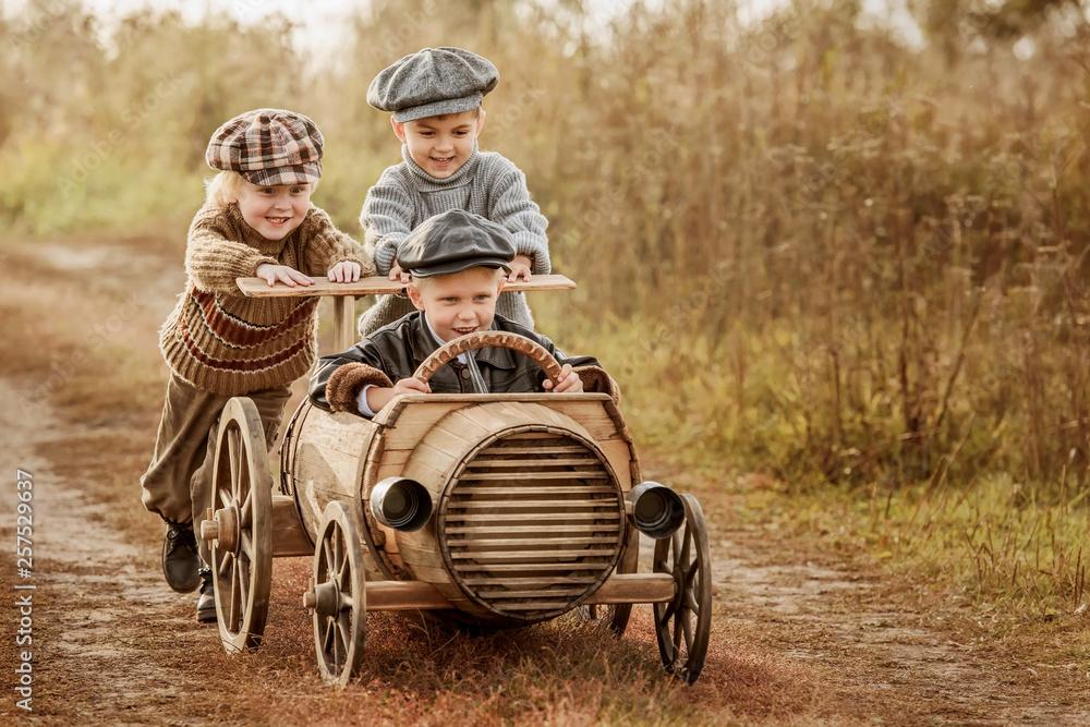 Children ride on a makeshift wooden racing car