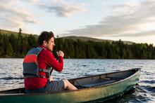 Man Paddling In Canoe On Lake