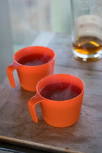 Hot Apple Cider With Bourbon In Orange Cups Inside The Pickett Butte Fire Lookout Near Tiller, Oregon, USA
