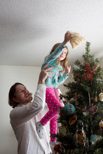 Father Helping Daughter Decorate Christmas Tree