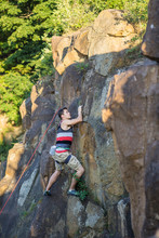 Rock Climber On Wall Reaching Forward