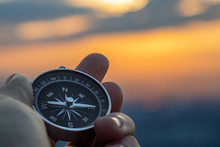 Compass In Hand With Sunset Sky On The Background