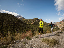 Happy Caucasian Couple Running Along Mountain Trial In Autumn