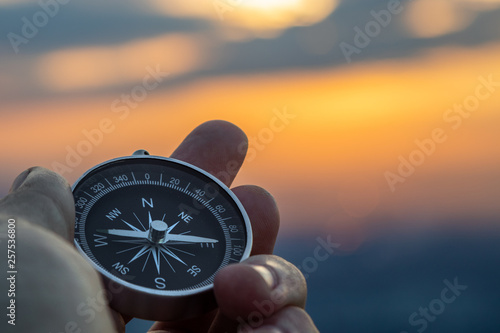 Fotografia compass in hand with sunset sky on the background