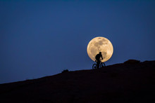 Silhouetted Bike Rider Riding In Front Of A Full Moon.