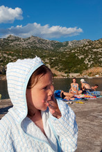 Girl In Hooded Bathrobe With Finger In Mouth On Beach