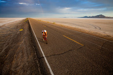Man Riding Bicycle Along Bonneville Salt Flats, Utah, USA