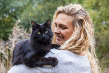 Portrait Of Black Cat On Shoulder Of Smiling Young Woman