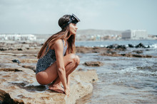 Woman In Swimsuit And Snorkeling Mask Crouching On Beach