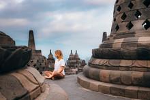 Woman Sitting Among Stupas At Borobudur Temple, Magelang, Central Java, Indonesia