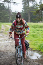Young Woman Riding Bike On Dirt Road