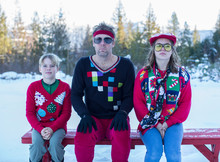 Father And Children Wearing Christmas Sweaters Outdoors