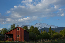 A Red Barn In Front Of A Mountain.