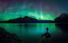 Silhouette Of Person Looking At Aurora Borealis Over Lake