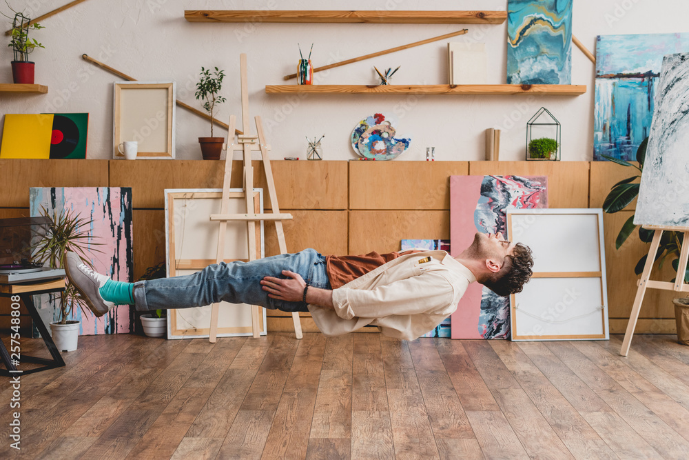 Fototapety, obrazy: handsome artist with closed eyes levitating over wooden floor in painting studio