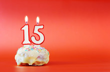 Fifteen Years Birthday. Cupcake With White Burning Candle In The Form Of Number 15. Vivid Red Background With Copy Space