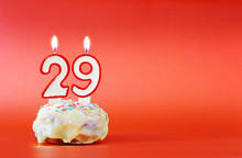 Twenty Nine Years Birthday. Cupcake With White Burning Candle In The Form Of Number 29. Vivid Red Background With Copy Space