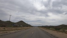 Driving POV Time Lapse Through Weathered Mojave Desert Road, Storm Clouds In Sky