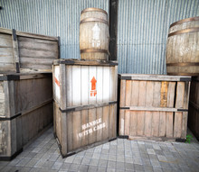 Old And Damage Vintage Wooden Box And Drum In Front Of Warehouse. One Box Has Handle With Care Written On It