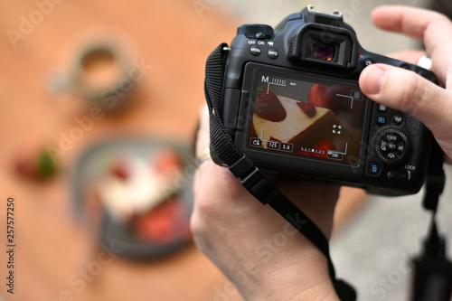 Fototapeta Hands of a photographer holding a camera, touching the screen with one finger taking photo of a cake on the plate and a cup of coffee in the blurred background. Closeup. obraz na płótnie