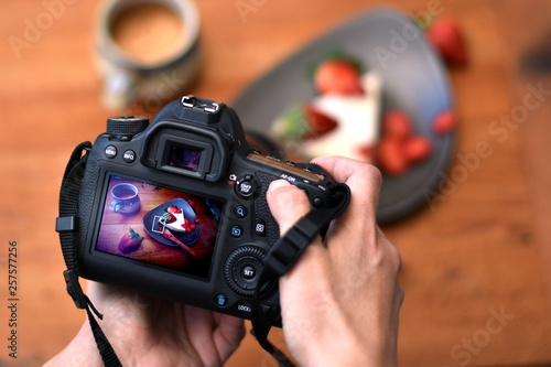 Fototapeta Hands of a photographer holding a camera with strawberry cake photo on the screen with the cake on the plate and a cup of coffee in the blurred background. Closeup. obraz na płótnie