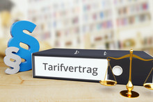 Tarifvertrag – Anwalt. Ordner Auf Schreibtisch Mit Beschriftung Neben Paragraf Und Waage. Arbeitsrecht