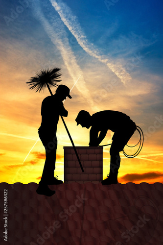 chimney sweep on the roof at sunset Canvas Print