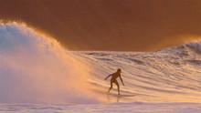 Yellow Evening Sunshine Illuminating The Scenic Nature And Surfer Riding Waves