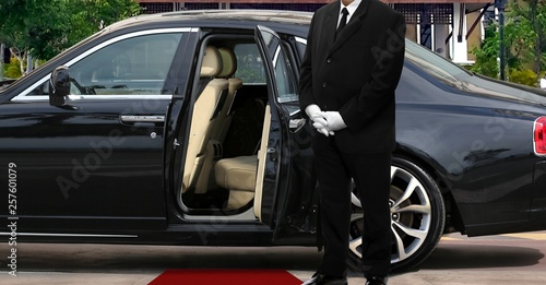 Limo driver standing next to opened car door with red carpet Poster Mural XXL