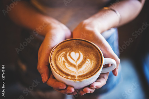 Photo sur Toile Cafe woman hold a cup of latte art coffee in hand at cafe, vintage tone