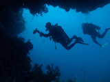 Two divers are silhouetted through cave and coral