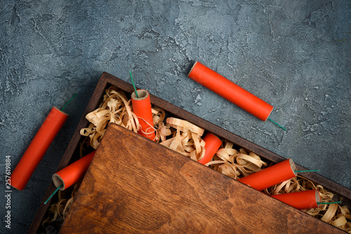 Valokuva  Red dynamite tnt firecrackers fuse in wooden box crate with wooden straw shavings