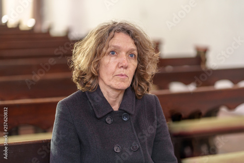 Fotografiet Religious woman sitting alone in a church pew