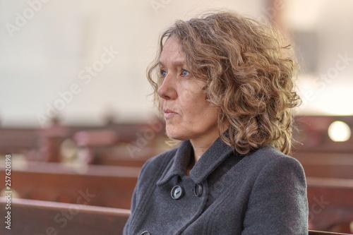 Canvastavla Religious woman sitting alone in a church pew