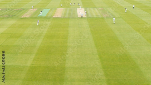 Fotografie, Obraz  Young boys playing test cricket with a red ball dressed in white