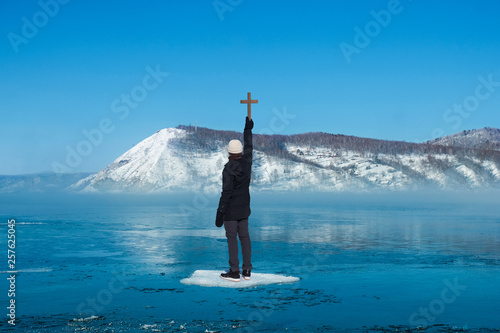 Man standing on ice floes floating in river in winter holding wooden cross with Canvas Print