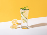 Mojito cocktail with lemon and mint in glass on yellow background. summer drink.