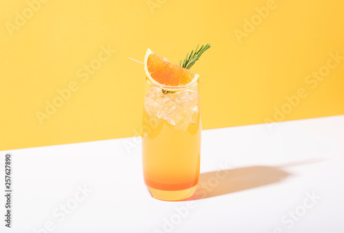 Papel de parede Cold and refreshing orange punch cocktail with orange slice on yellow background