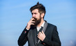 Recovery from nicotine addiction must involve changing our relationship to smoking. Bearded hipster smoking cigarette blue sky background. Guy enjoy cigarette. Man beard and mustache hold cigarette