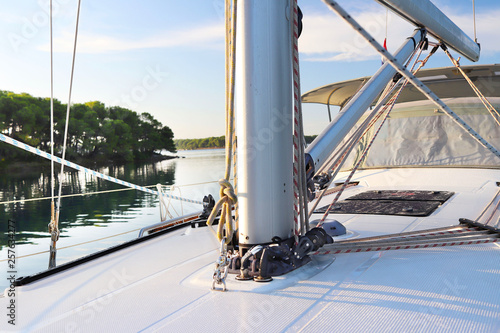 Fototapeta  The mainmast is a mast and a twirled staysail on a sailing yacht and bow rails against the backdrop of a picturesque green bay with a yacht anchored