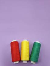 Colored Sewing Thread On Purple Frosted Fabric Background. Selective Focus.